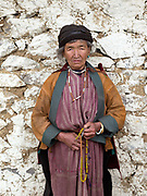 Portrait of a Brokpa woman wearing her traditional clothing outside the temple on an 'auspicious day' in the remote village of Merak in Eastern Bhutan. The Brokpa, the semi-nomads of the villages of Merak and Sakteng are said to have migrated to Bhutan a few centuries ago from the Tshona region of Southern Tibet. Thriving on rearing yaks and sheep, the Brokpas have maintained many of their unique traditions and customs.
