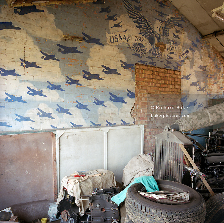 A wall mural of WW2 bombers crossing the sky and wreck of a Rolls-Royce at the former RAF Hethel air for base in Norfolk, England. Built during 1942 for use by the Americans and was transferred to the USAAF from 14 September 1943 though to 12 June 1945. Hethel served as headquarters for the 2nd Combat Bombardment Wing of the 2nd Bombardment Division. The group flew B-24 Liberators as part of the Eighth Air Force's strategic bombing campaign.  Strategic objectives in France, the Low Countries, and Germany included targets such as shipbuilding yards at Vegesack, industrial areas of Berlin, oil facilities at Merseburg, factories at Münster, railroad yards at Sangerhausen, and V-weapon sites in the Pas de Calais. After the war, the buildings reverted to agricultural and industrial use.