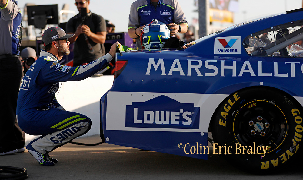 Jimmie Johnson squats behind his car as he waits to qualify for the NASCAR Cup Series auto race at Kansas Speedway in Kansas City, Kan., Friday, Oct. 20, 2017. (AP Photo/Colin E. Braley)