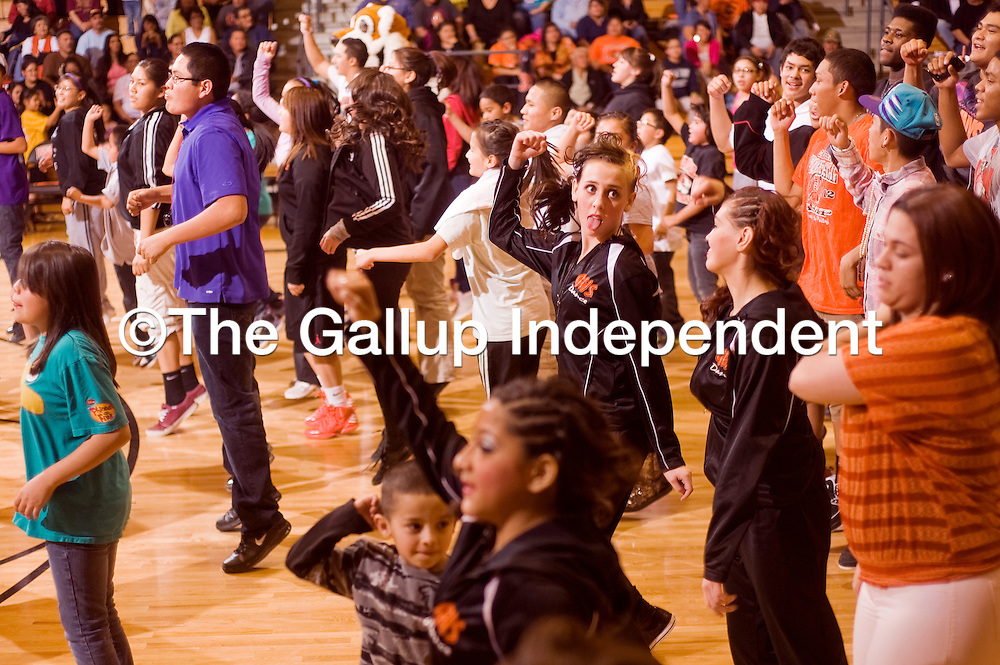020513       Cable Hoover<br /> <br /> Gallup High School freshman Mariah Gonzales, center, and other dance team members dance with a crowd of audience participants during half-time of the Gallup and Miyamura girls basketball game at Gallup High School Tuesday.