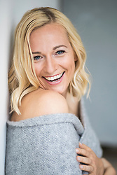 Portrait of happy young woman leaning against wall
