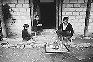 Two men and a young boy sit together on small benches in Xa Phin Market, Ha Giang Province, Vietnam, Southeast Asia