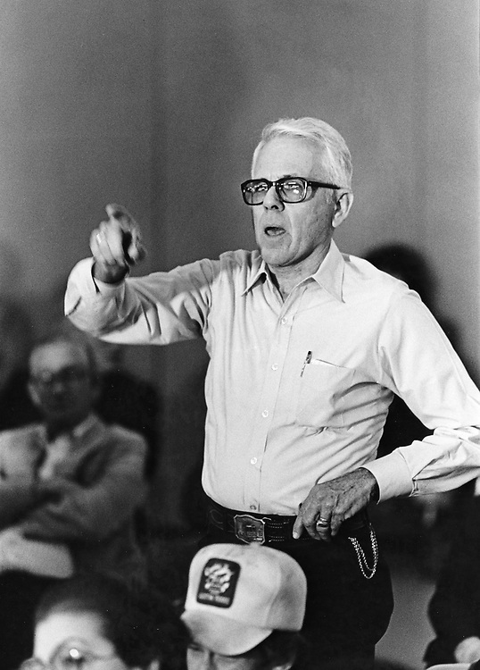 ©1990 SPEAKING UP IN PUBLIC SITUATIONS: Man making a point at public hearing on airport expansion issues.