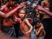 24 OCTOBER 2015 - YANGON, MYANMAR: A Shia boy participates in ritual self flagellation with razors and chains during Ashura observances at Mogul Mosque in Yangon. Ashura commemorates the death of Hussein ibn Ali, the grandson of the Prophet Muhammed, in the 7th century. Hussein ibn Ali is considered by Shia Muslims to be the third imam and the rightful successor of Muhammed. He was killed at the Battle of Karbala in 610 CE on the 10th day of Muharram, the first month of the Islamic calendar. According to Myanmar government statistics, only about 4% of the population is Muslim. Many Muslims have fled Myanmar in recent years because of violence directed against Burmese Muslims by Buddhist nationalists.     PHOTO BY JACK KURTZ