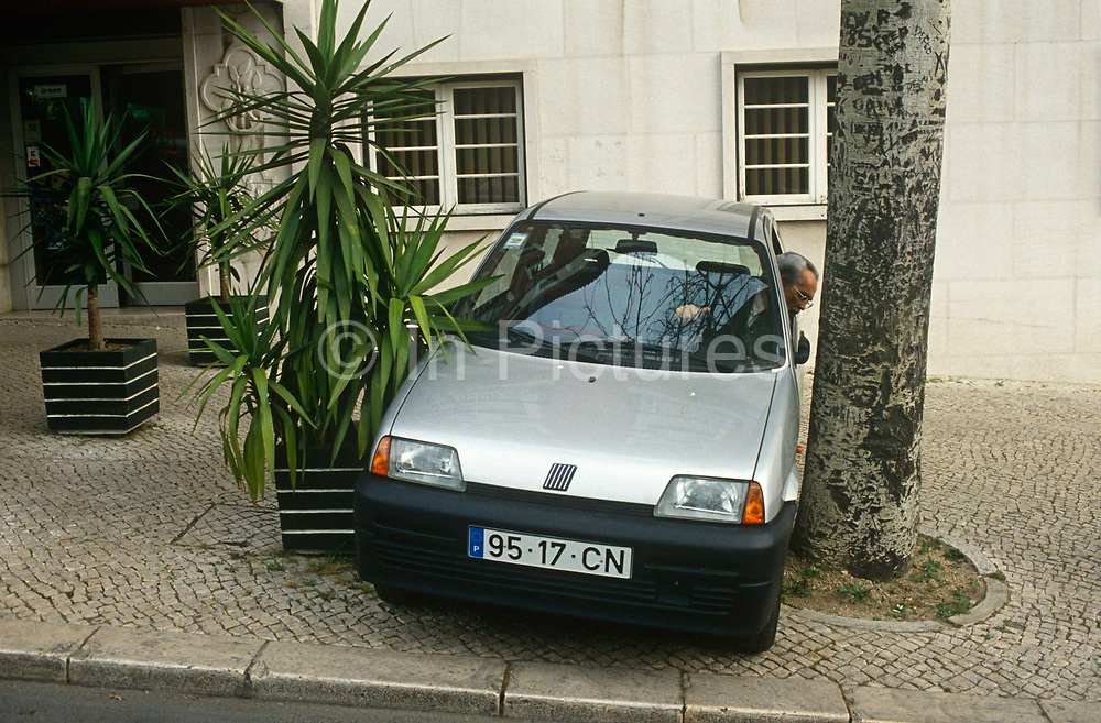 A local Portuguese man reverses his Fiat car into a narrow space between two trees on a Lisbon street pavement. Squeezing between the shrub and the tree, the elderly man deftly positions his vehicle outside his apartment block in a suburb of the Portuguese suburb. He leans out through an open window to see his exact gap between the tree trunk and the paintwork of his door.