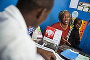 Katy Cherif, 40, and her twin sons Lacine (not seen) and Lusseini, both 4 and suffering from malaria and diarrhea, meet with a nurse at the Libreville health center in Man, Cote d'Ivoire on Wednesday July 24, 2013.