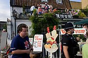Large spectator and fat policeman on the first day of competition of the London 2012 Olympic 250km mens' road race. Starting from central London and passing the capital's famous landmarks before heading out into rural England to the gruelling Box Hill in the county of Surrey. Local southwest Londoners lined the route hoping for British favourite Mark Cavendish to win Team GB first medal but were eventually disappointed when Kazakhstan's Alexandre Vinokourov eventually won gold.
