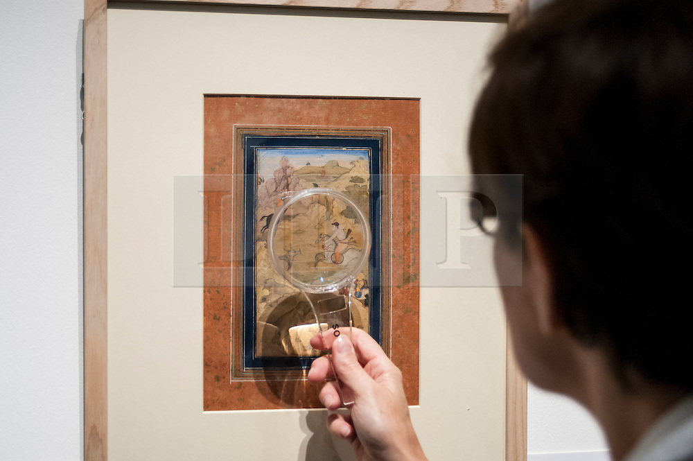 © Licensed to London News Pictures. 02/10/2015. London, UK. A visitor uses a magnifying glass to view one of the 157 Sven Gahlin Collection finely painted Indian miniature paintings at the preview of Indian and Islamic Art Week at Sotheby's which runs from 2 to 7 October.   Photo credit : Stephen Chung/LNP
