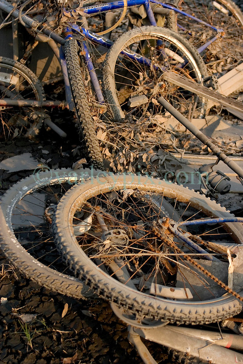 30 Sept, 2005.  New Orleans, Louisiana. Lower 9th ward. Hurricane Katrina aftermath. <br /> The remnants of the lives of ordinary folks, now covered in mud as the flood waters recede. Bicycles piled together in the dirt..<br /> Photo; ©Charlie Varley/varleypix.com