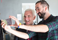 © Licensed to London News Pictures . 25/09/2016 . Liverpool , UK . Shadow Chancellor JOHN MCDONNELL poses for a selfie with LIAM KELLY (right) , director of Make Liverpool , during a visit . Make Liverpool is an open access workshop and maker space , free to use for the people of North Liverpool , on Trafalgar Dock , during the first day of the Labour Party Conference . Photo credit : Joel Goodman/LNP