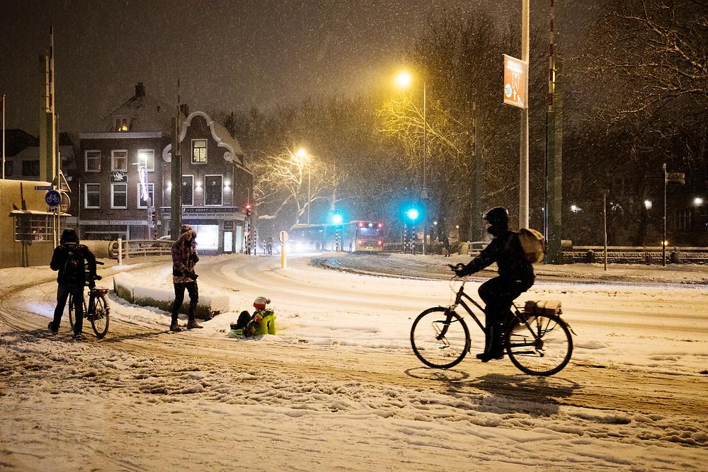 In Utrecht rijden en lopen fietsers door de sneeuw. Door hevige sneeuwval is het verkeer ontregeld. Ondanks het strooien zijn veel wegen en fietspaden nauwelijks berijdbaar.<br /> <br /> In Utrecht cyclists ride in the snow. Due to heavy snowing the traffic has lots of problems, even though the roads are de-iced most of the roads and bike lanes are hard to ride on.