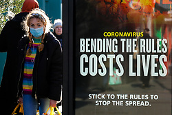 © Licensed to London News Pictures. 22/01/2021. London, UK. A woman wearing a protective face covering walks past the government's 'Bending the rules costs lives' publicity campaign poster in north London. The Office for National Statistics (ONS) has released figures which show the percentage of people testing positive for the virus decreased slightly in the week ending 16 January. During that period, an estimated one in 30 people had Covid-19 in London. Photo credit: Dinendra Haria/LNP