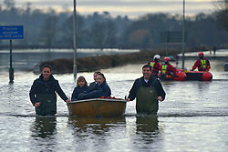 © Licensed to London News Pictures. 10/02/2014. Old Windsor, UK . School children are ferried by boat. Flooding in OLD WINDSOR in Berkshire today 10th February 2014 after the River Thames burst its banks. The Environment Agency has issued 14 Severe Flood Warnings alone the Thames. Photo credit : Stephen Simpson/LNP