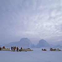 BAFFIN ISLAND, NUNAVUT, CANADA. Inuit guides, snowmobiles & Great Sail Peak expedition members beside icebergs on frozen Baffin Bay.