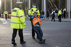 © Licensed to London News Pictures. 25/10/2021. London, UK. An Insulate Britain climate change activist being for blocking traffic on Bishopsgate in the City of London. The group have restarted their actions to block motorways and major roads causing disruption in the week before the COP26 climate meeting in Glasgow on 31/10/2021. Photo credit: Ben Cawthra/LNP