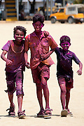 Indian boys celebrating annual Hindu Holi festival of colours smeared with powder paints on beach by Marine Drive in Mumbai, India