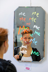 """© Licensed to London News Pictures. 31/03/2017. London, UK.  A visitor views """"Me, Me, Me"""", one in the series of """"Will I Ever Make It"""" mirror works by Graham Messer Opening day of The Other Art Fair, presented by Saatchi Art, which runs until 2 April in Bloomsbury.  The fair is collection of artworks by 120 emerging artists selected by a committer of art experts including Lulu Guinness OBE, Kate Bryan, Head of Collections at Soho House Group, and Rebecca Wilson, Chief Curator of Saatchi Art. Photo credit : Stephen Chung/LNP"""