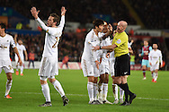 The Swansea city players crowd around referee Lee Mason as they appeal for a penalty after the ball had appeared to hit the arm of West Ham defender James Collins who blocked a shot from Ki Sung-Yueng of Swansea city (c).Barclays Premier league match, Swansea city v West Ham Utd at the Liberty Stadium in Swansea, South Wales  on Sunday 20th December 2015.<br /> pic by  Andrew Orchard, Andrew Orchard sports photography.