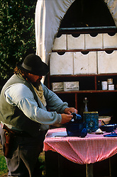 man cooking at a table on an old western covered wagon