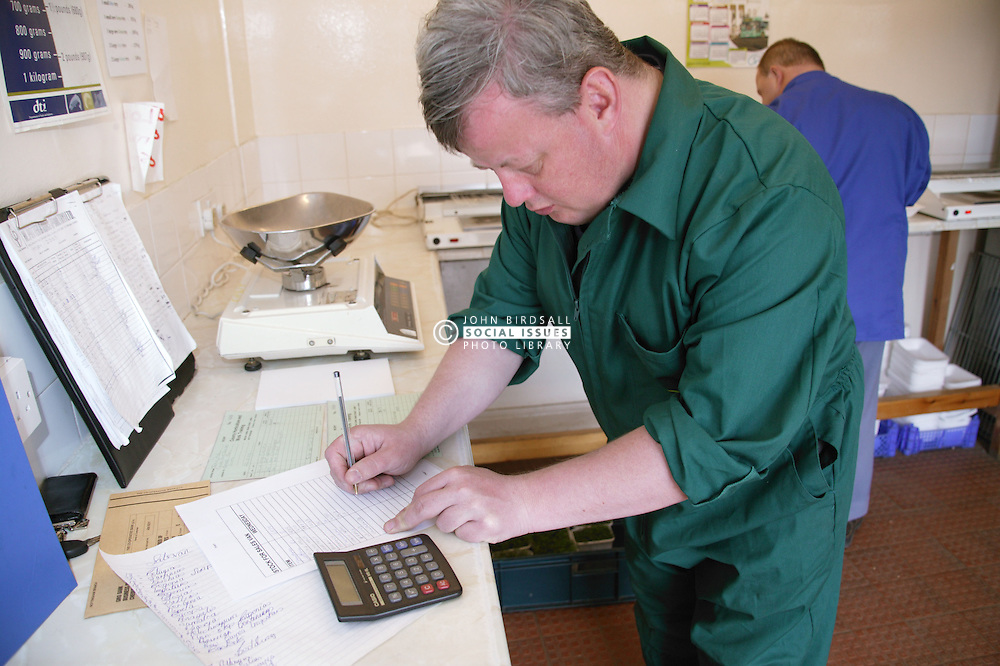 Man with learning disability at work at Brook Farm; Linby; using calculator,