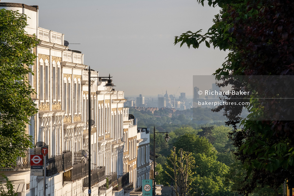 With the London skyline in the far distance, homes line the steep gradient of Gypsy Hill in Crystal Palace, on 16th June 2021, in London, England.