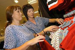 Two female shop workers in women's clothes shop; Merseyside; UK