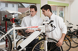 Mechanics testing electric bicycle with laptop
