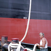Deck hand on a tugboat in Boston harbor secures a line from a tanker to a large cleat on his boat