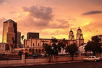 Downtown Tucson at sunset with a yellow sky. St. Augustine is in the foreground