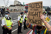 Metropolitan Police officers form a line in front of Kill the Bill activists on Westminster Bridge protesting against the Police, Crime, Sentencing and Courts PCSC Bill 2021 as MPs consider amendments to the Bill in the House of Commons on 5th July 2021 in London, United Kingdom. The PCSC Bill would grant the police a range of new discretionary powers to shut down protests, including the ability to impose conditions on any protest deemed to be disruptive to the local community, wider stop and search powers and sentences of up to 10 years in prison for damaging memorials.
