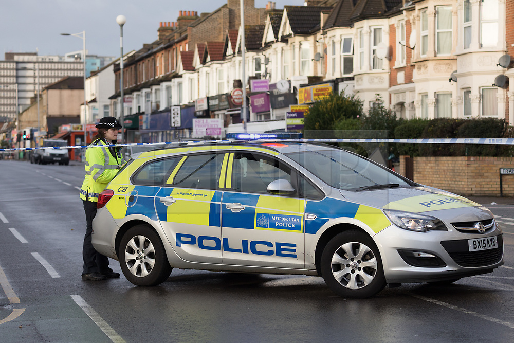 © Licensed to London News Pictures. 12/11/2017. LONDON, UK.  Police car and police officer at the police cordon and crime scene at High Road in Ilford. At 02:48 this morning, police were called to the scene, where a man had been beaten by a group of men with what is thought to have been baseball bats. The man was taken to an east London hospital by London Ambulance Service where he died at 04:35.  Photo credit: Vickie Flores/LNP