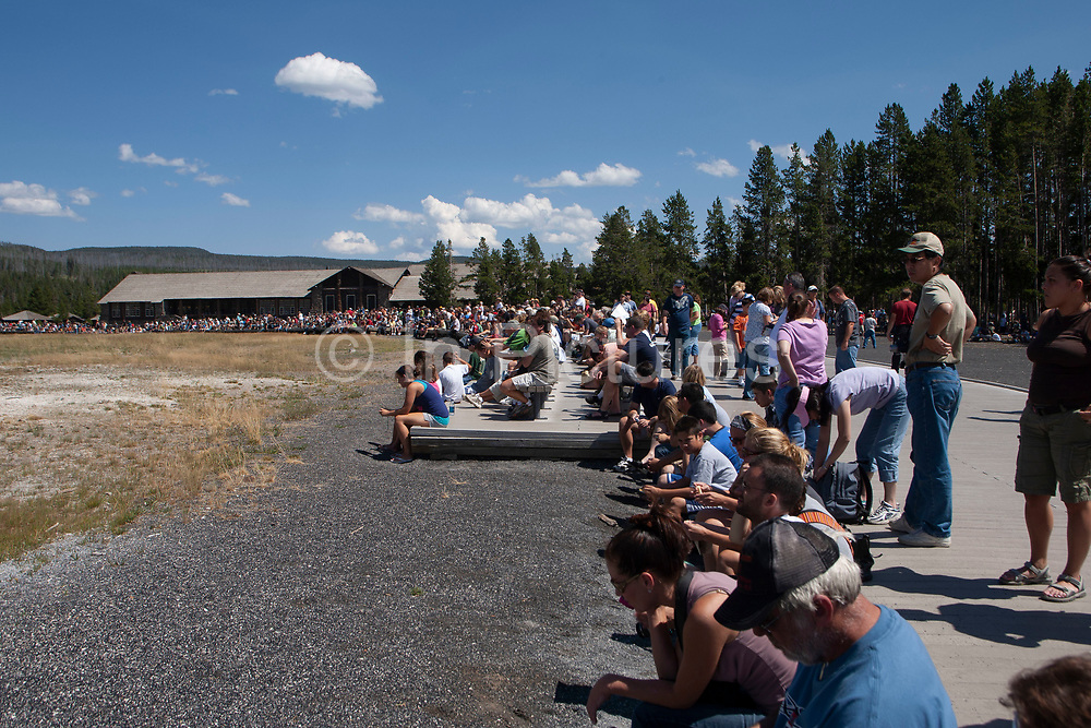 The Washburn Expedition in 1870 named Old Faithful for its regular schedule of eruptions and is the grand old geyser of Yellowstone National Park which this crowd are awaiting, on 7th August 2007 in Wyoming, United States. The intervals between eruptions average between 45-90 minutes and the average duration is about four minutes. To predict the next eruption, its first continuous surge is timed until the final splash.
