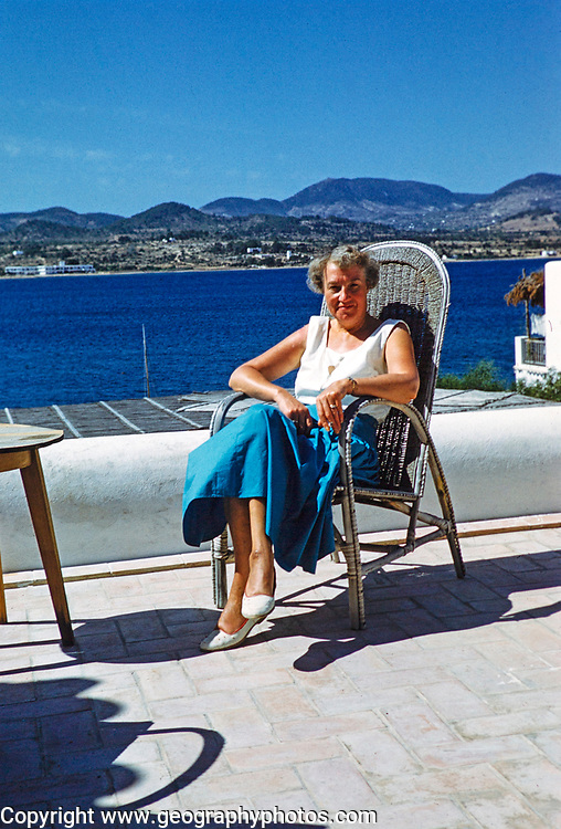 Middle aged female tourist sitting in sun on terrace by the sea, island of Ibiza, Balearic Islands, Spain, 1950s