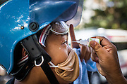 26 DECEMBER 2013 - BANGKOK, THAILAND: A protestors gets his eyes rinsed out after he was hit by tear gas during a riot at the Thai Japan Stadium in Bangkok. Thousands of anti-government protestors flooded into the area around the Thai Japan Stadium to try to prevent the drawing of ballot list numbers by the Election Commission, which determines the order in which candidates appear on the ballot of the Feb. 2 election. They were unable to break into the stadium and ballot list draw went as scheduled. The protestors then started throwing rocks and small explosives at police who responded with tear gas and rubber bullets. At least 20 people were hospitalized in the melee and one policeman was reportedly shot by anti-government protestors.      PHOTO BY JACK KURTZ