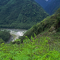 Tibet's Tsangpo River (Brahmaputra) turns abruptly east after flowing north between two 23-000+ foot peaks in the Tsangpo Gorge, one of the world's deepest canyons. In the foreground it merges with the Po Tsangpo River. Clouds hide Mount Namcha Barwa.