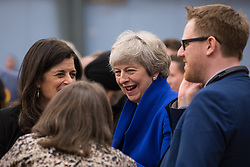 Maidenhead, UK. 13 December, 2019. Former Prime Minister Theresa May (Conservative) shares a joke with colleagues at the general election count for the Maidenhead constituency.