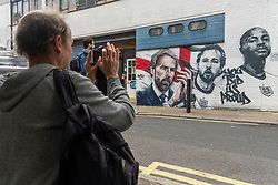 © Licensed to London News Pictures. 14/07/2021. London, UK. A man takes a photo of the mural of England football team including manager GARETH SOUTHGATE and footballers HARY KANE and RAHEEM STIRLING has been unveiled near London. Bridge. The mural created by Marc Silver of MurWalls, is a celebration of a team that has united the nation. Photo credit: Ray Tang/LNP