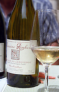 A bottle and glass of Domaine Rimbert, owned by the winemaker Jean-Marie Rimbert who is sitting in the background, Saint-Chinian, Coteaux du Languedoc, Languedoc-Roussillon, France