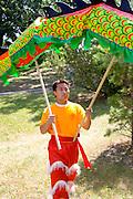 Dance team member helps hold ceremonial dragon with two poles. Dragon Festival Lake Phalen Park St Paul Minnesota USA
