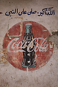 Detail of an old Coca-Cola mural on a wall at the weekly market at Qurna, a village on the West Bank of Luxor, Nile Valley, Egypt. Arabic writing is above the famous brand name showing the cultures that the US company's presence reaches.