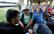 Migrants are seen on a train travelling from Budapest to Gyor, Hungary, September 3 2015. An estimated 3,000 people were believed to be camped out at the station as authorities opened the doors to those without European visas or travel documents to board trains.