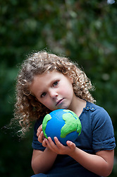 young girl holding a model of planet Earth and showing concern for future