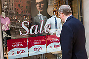 A British man window shops during his lunch break in London, United Kingdom.  He is looking at the clothes in the shop front which are on sale.