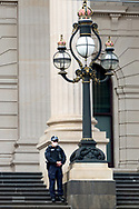 A police officer stands on the steps of Parliament building to keep an eye on protesters on 06 June, 2020 in Melbourne, Australia. This event was organised to rally against aboriginal deaths in custody in Australia as well as in unity with protests across the United States following the killing of an unarmed black man George Floyd at the hands of a police officer in Minneapolis, Minnesota. (Photo by Mikko Robles/ Speed Media)