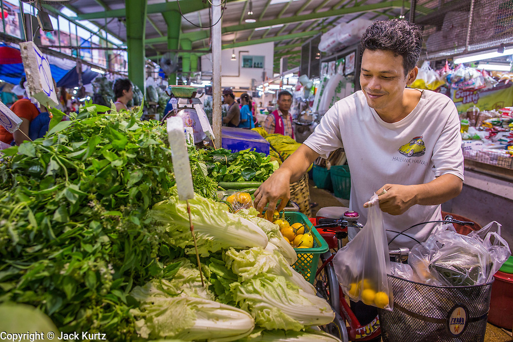 """03 OCTOBER 2012 - BANGKOK, THAILAND:      A man shops for vegetables in Khlong Toey Market in Bangkok. Khlong Toey (also called Khlong Toei) Market is one of the largest """"wet markets"""" in Thailand. Thousands of people shop in the sprawling market for fresh fruits and vegetables as well meat, fish and poultry every day.      PHOTO BY JACK KURTZ"""