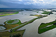 Nederland, Noord-Brabant, Werkendam, 23-10-2013; landschapskunstwerk De Wassende Maan van kunstenaar Paul de Kort: afhankelijk van het getij staan de spiralen van het labyrint meer of minder onder water. Het kunstwerk ligt in polder de Noordwaard in de Biesbosch. In het kader van Ruimte voor de Rivier' (bescherming tegen hoogwater door rivierverruiming) is de dijk van de Merwede gedeeltelijke afgraven (onder in beeld). Doel is het maken van een doorstroomgebied (naar rechtsboven), bij hoge waterstanden zal het water van de Nieuwe Merwede afgeleid worden en zo westelijk naar het Hollandsch Diep afgevoerd worden. De kans op overstromingen (in de bovenloop) is hierdoor kleiner.<br /> Landart from artist Paul de Kort, Growing Moon: depending on the height of the tide, the spiral willl be more or less visible. The art work lies in Polder Noordwaard (part of Biesbosch National Park), part of the program 'Room for the River' (protection against high water by means of creating space for rivers). The former polder can store water and allows the river to flood more easily downstream. These measures dimishes the risk of floods further upstream at high water in the winter. <br /> luchtfoto (toeslag op standard tarieven);<br /> aerial photo (additional fee required);<br /> copyright foto/photo Siebe Swart
