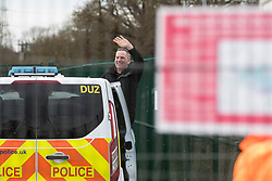 Harefield, UK. 18 February, 2020.  Partially-sighted former Paralympic cyclist James Brown of Extinction Rebellion waves from a Metropolitan Police vehicle following his arrest at a HS2 site in the Colne Valley. He was arrested after locking himself with a fellow activist onto a drilling rig which environmental activists believe will be used to drill into the aquifer which supplies 22% of London's drinking water, risking contamination.
