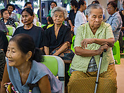 15 DECEMBER 2016 - PRACHINBURI, THAILAND: People wait for their cash disbursements in a government credit union in Prachinburi, Thailand. The Thai government said people who earn 30,000 Baht (about $857 US) or less per year are entitled to a 3,000 Baht cash payment (about $85.7 US) and those who earn 30,000 Baht to 100,000 Baht (about $2,857 US) per year are entitled to a 1,500 Baht (about $42.8 US) cash payment. The plan is meant to help low income people, especially the rural poor. Government banks in rural areas offering the disbursement have been crowded with people seeking their payments this week.      PHOTO BY JACK KURTZ   Social Safety Net