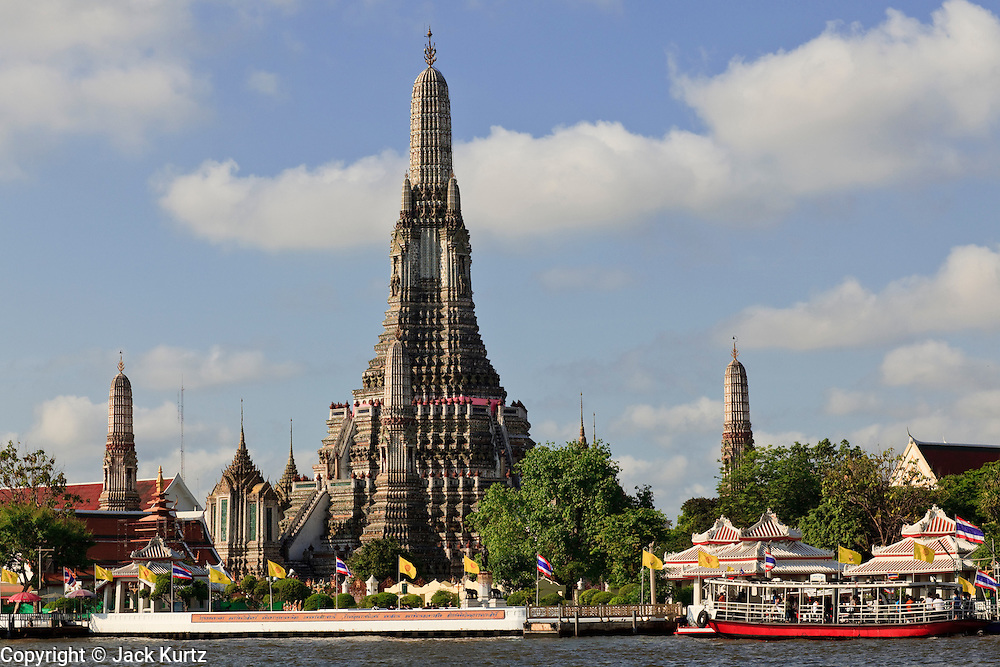 """09 MARCH 2009 -- BANGKOK, THAILAND:  Wat Arun is a Buddhist temple (wat) in the Bangkok Yai district of Bangkok, Thailand, on the west bank of the Chao Phraya River. The full name of the temple is Wat Arunratchawararam Ratchaworamahavihara. The outstanding feature of Wat Arun is its central prang (Khmer-style tower). It may be named """"Temple of the Dawn"""" because the first light of morning reflects off the surface of the temple with a pearly iridescence. Steep steps lead to the two terraces. The height is reported by different sources as between 66,80 m and 86 m. The corners are surrounded by 4 smaller satellite prangs. The prangs are decorated by seashells and bits of porcelain which had previously been used as ballast by boats coming to Bangkok from China. The central prang is topped with a seven-pronged trident, referred to by many sources as the """"trident of Shiva"""". Around the base of the prangs are various figures of ancient Chinese soldiers and animals. Over the second terrace are four statues of the Hindu god Indra riding on Erawan. The temple was built in the days of Thailand's ancient capital of Ayutthaya and originally known as Wat Makok (The Olive Temple). In the ensuing era when Thonburi was capital, King Taksin changed the name to Wat Chaeng. The later King Rama II. changed the name to Wat Arunratchatharam. He restored the temple and enlarged the central prang. The work was finished by King Rama III. King Rama IV gave the temple the present name Wat Arunratchawararam. As a sign of changing times, Wat Arun officially ordained its first westerner, an American, in 2005. The central prang symbolizes Mount Meru of the Indian cosmology. The satellite prangs are devoted to the wind god Phra Phai..Photo by Jack Kurtz"""