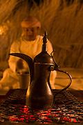 Man, preparing Arabic coffee in the desert, United Arab Emirates